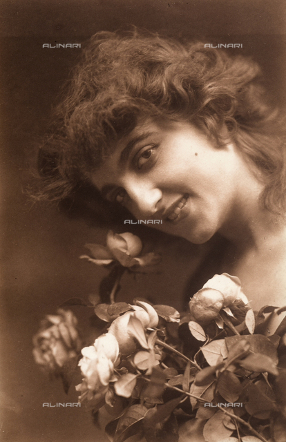 Portrait of a young woman, smiling and biting her lower lip. In the foreground, there is a bouquet of roses.