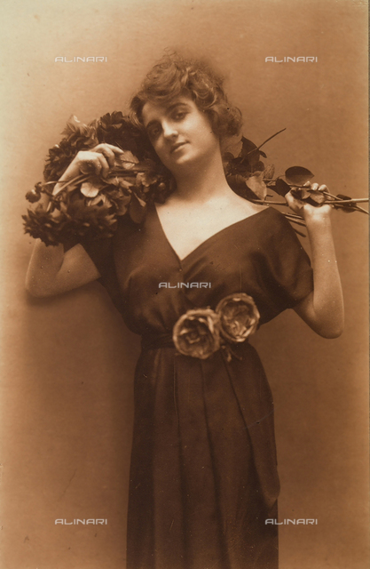 Portrait of a young woman wearing a dark dresswith a plunging neckline. Two peonies are decorating the belt on her dress, and in her hand she holds a bouquet of dahlias, lightly resting on her shoulder