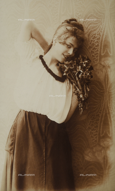 Portrait of a smiling, young woman in a provocative pose. Her right hand rests on the base her head while her left hand hold a bouquet of flowers near her face