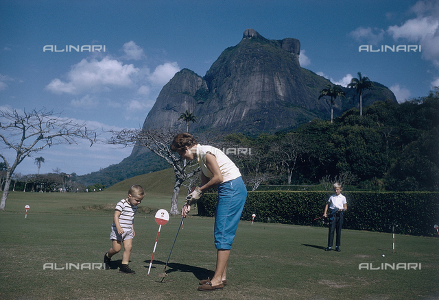 Young woman with two children on a putting green; America