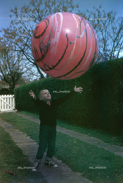 Little boy playing with a giant balloon; America
