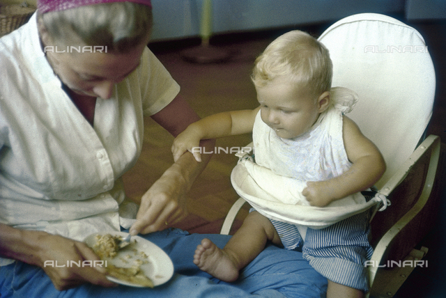 Baby taking food from his mother; America
