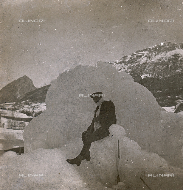 Man posing on a frozen fountain with the mountains of Cortina d'Ampezzo in the background