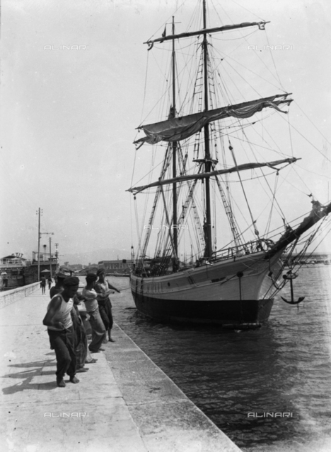 Sailors working to pull a sailboat to the dock of Viareggio