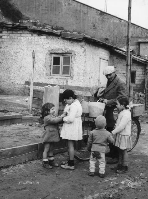 """Group of children around a """"fusaiaro"""" (seller fusaie) in the district Valle Aurelia"""