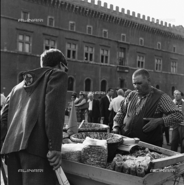 Vendor of peanuts, tree nuts and olives in Piazza Venezia in Rome during the funeral of Palmiro Togliatti August 25, 1964