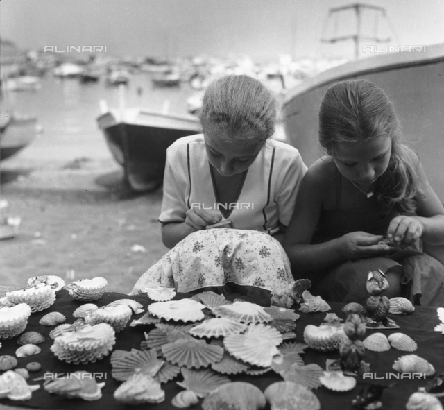 Pair of girls that decorate shells in Porto Ercole in Monte Argentario