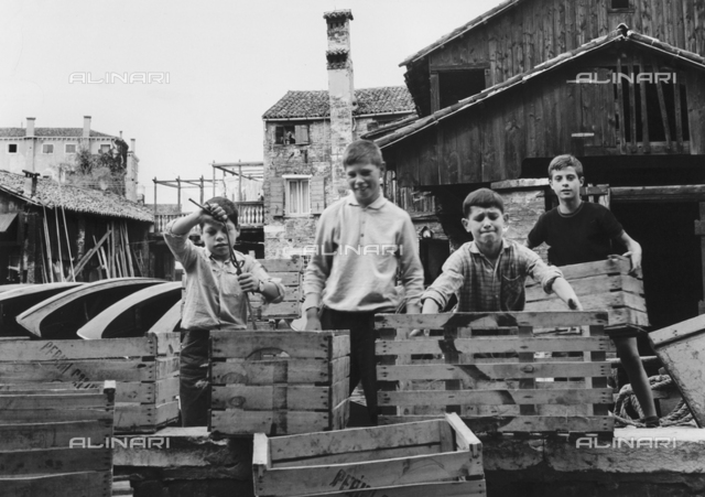 San Trovaso boatyard in Venice: a group of children carrying wooden crates
