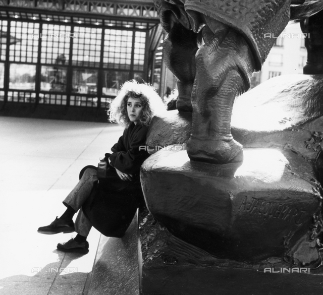 Woman sitting on the base of the sculpture of Jacoumart in front of the Musée d'Orsay in Paris