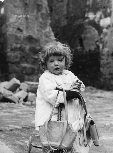 Little girl with tricycle in Sovana