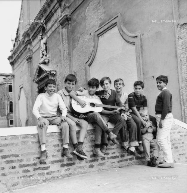 Group of children singing and playing guitar on a bridge in Venice