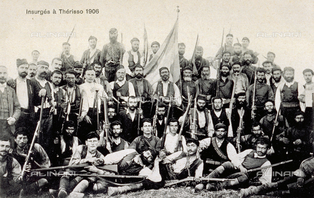 Portrait of a group of greek rebels. They are posing armed with rifles. At the center of the group the greek flag