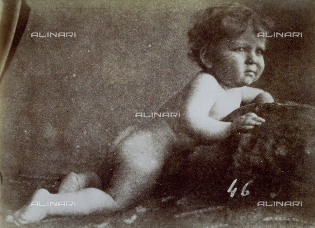Full-length portrait of a nude child half-reclining on pillows