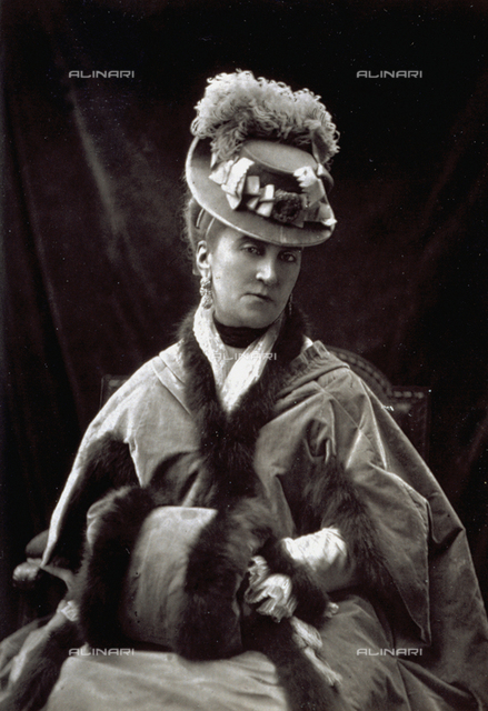 Half-length portrait of the actress Eugenie Doche. She is wearing a cape and a muff edged with fur and is wearing a small hat with a feather