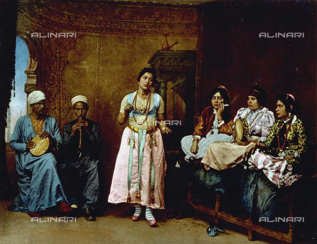 Portrait of a young egyptian dancer accompanied by a group of arab singers and two musicians in ethnic dress