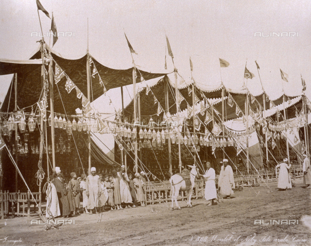 Group of egyptian men and boys shown inside an enclosure marked by a canopy decorated with lanterns and banners, set up for an arab feast