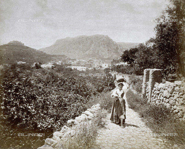 A country road on the island of Capri. In the foreground a young woman carrying two pitchers. In the background the town at the base of high ridges