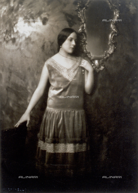 Full-length portrait of a young woman in evening clothes of the Twenties. The woman is standing against a wall with a mirror at her side