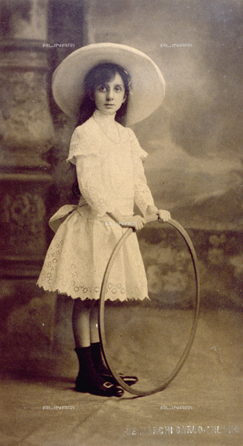Full-length portrait of a little girl in elegant light colored dress, a wide-brimmed hat and necklace. She is holding a large wooden hoop.