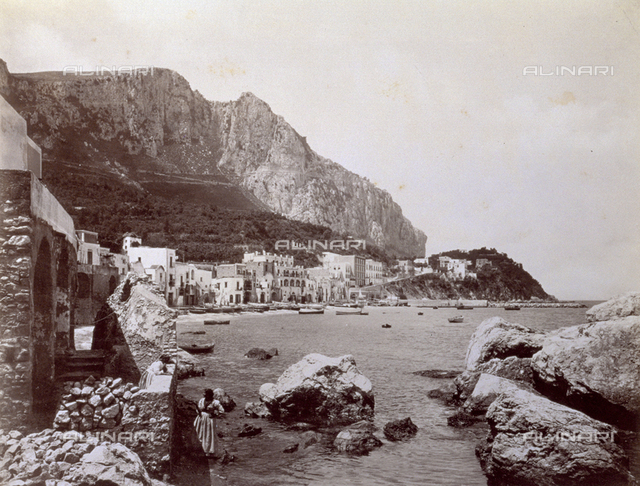 View of Marina Grande in Capri. In the foreground two women in traditional dress; Monte Solaro in the background