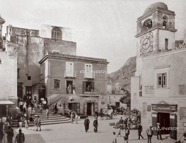 The piazza in Capri with Palazzo del Telegrafo and a few shops; on the left, the Clock Tower