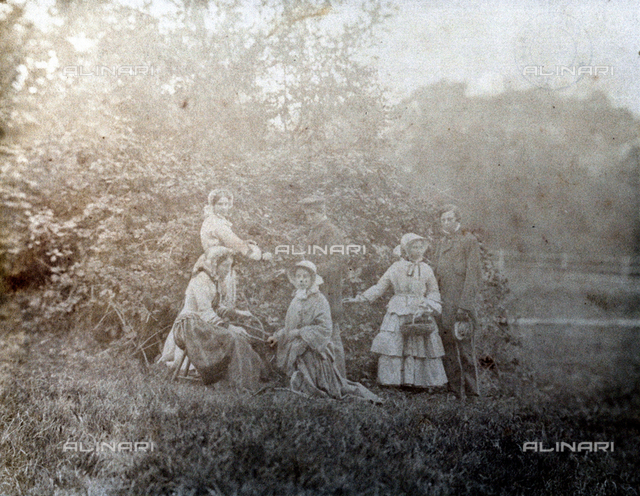 Group of men and women in a field. One of the ladies is sitting while another one is kneeling in front of her. Behind them, standing, the other figures