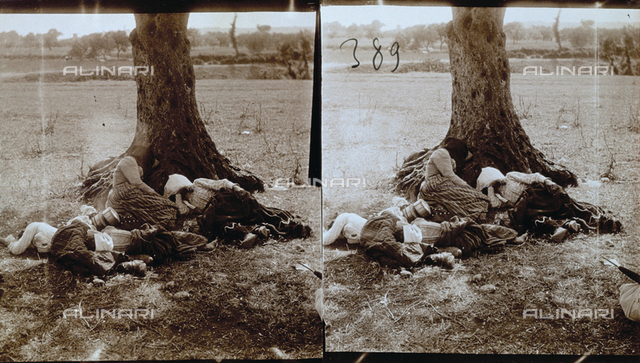 Group of farm workers in work clothes, lying on the grass, resting, at the foot of a tree