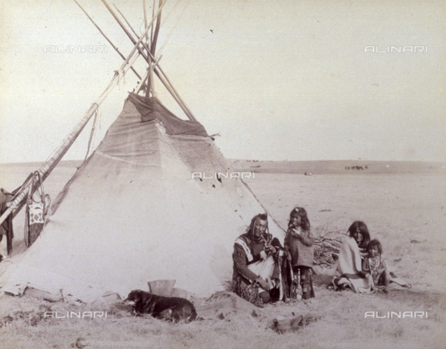 Family of Native Americans composed of father, mother and two children. They are shown seated with their dog in front of their tent