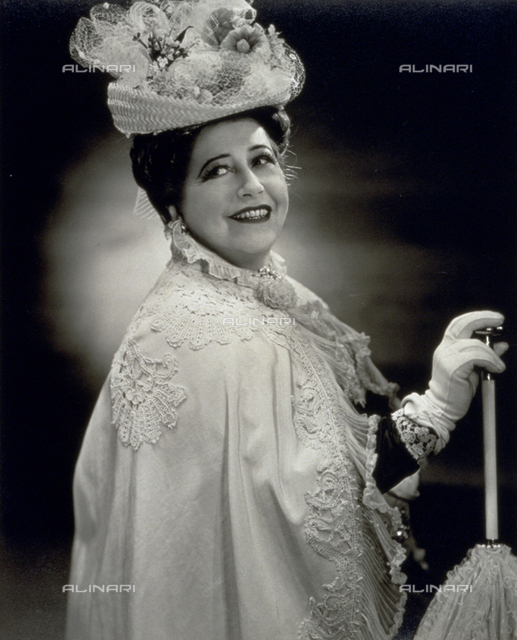 Half-length portrait of a woman in stage dress consisting of a mantle decorated with lace, gloves and an elaborate small hat. She is holding a closed umbrella in her right hand