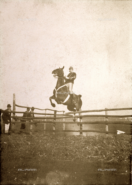 Portrait of a soldier in uniform taken just as his horse jumps an obstacle