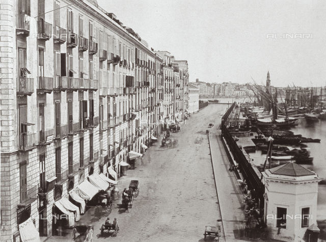 Panorama of Messina: on the right, the port with boats moored; at the center, the road that skirts it, with gigs travelling on it; to the right, a dense row of buildings