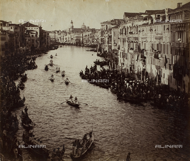 Grand Canal, in Venice, crowded with people for a historic regatta. The windows of the buildings are decked with flags