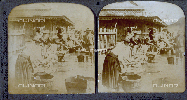 Fish market in Lisbon. Women wearing flat hats sell fish from wooden boxes
