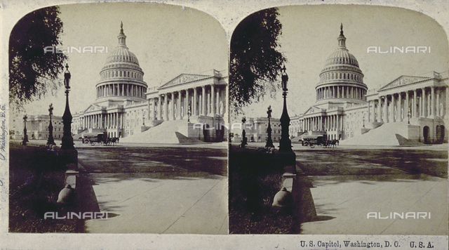 View of the Capitol building in Washington D.C. with its imposing dome. In the foreground an avenue lined with lamp-posts with a carriage travelling along it
