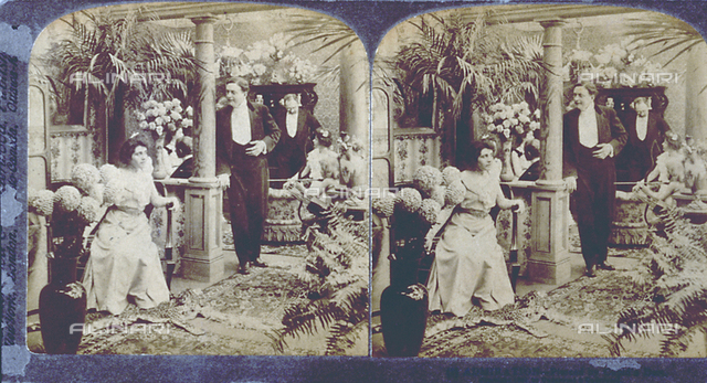 Genre scene. In an interior full of plants, a man, leaning against a column is looking at a young woman seated in an arm chair. In the background, another couple