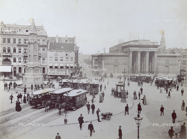 The Dam promenade in Amsterdam. The square is filled with people and parked trams with the large monument rising up in the background on the right, the stock market building