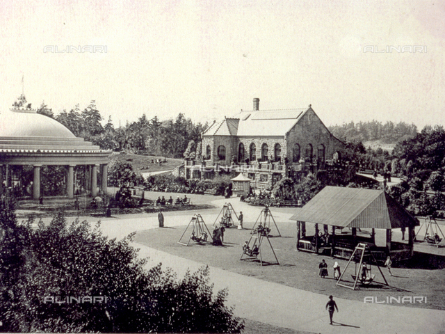 View of the 'Golden Gate Park' in San Francisco.In the foreground, a pavilion and swings with children playing. In the background a house surrounded by greenery
