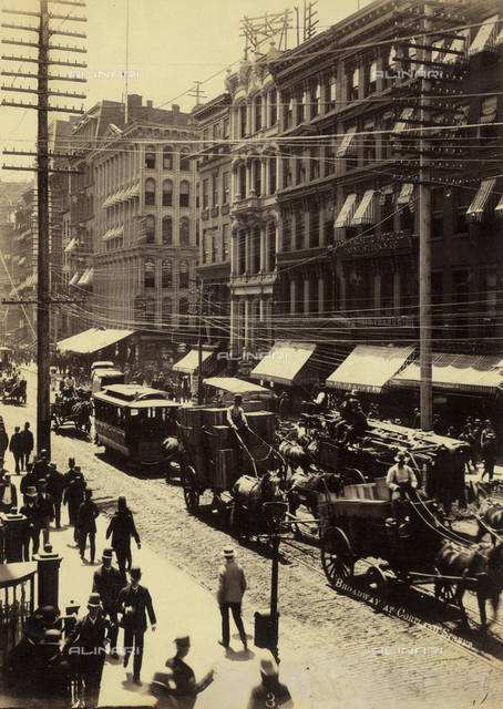 A street in New York crowded with pedestrians and horse-drawn carriages. At the sides of the street electric poles and lines