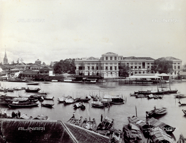 Panorama of Singapore. In the foreground a river with boats at anchor. In the background numerous buildings
