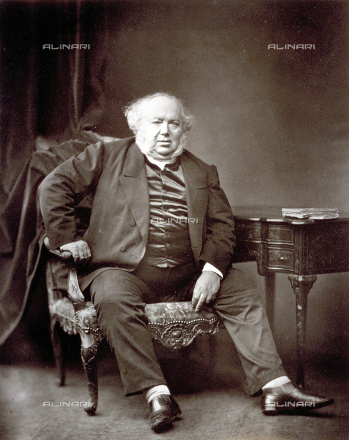 Portrait of Jules Janin sitting in armchair, besides a writing desk, dressed in jacket and satin vest. His face, with receding hairline, is framed by long white sideburns