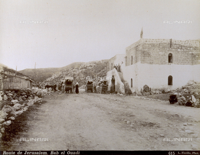 Middle eastern travellers with carts and horses on the road for Jerusalem. A poor house stands along the road where there are some people sitting