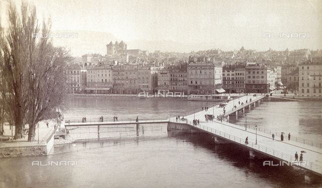 View of Geneva. In the foreground the lake. Two bridges which cross it with people walking. Trees and, in the background, the city buildings
