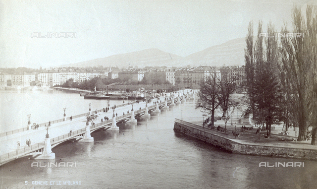 Panorama of Geneva. In the foreground the lake. On the right trees and on the left a bridge. In the background the buildings of the city