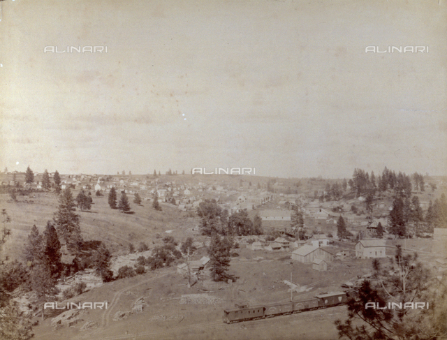 Panoramic view of a village in North America. In the foreground a train is running along the tracks, near a building site. To the left, wood is being transported on the waters of a river