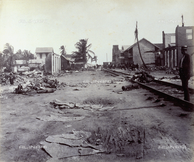 A street in Colon (Panama), strewn with rubble. In the foreground railroad tracks and on the right a man in a straw hat. In the background a few houses