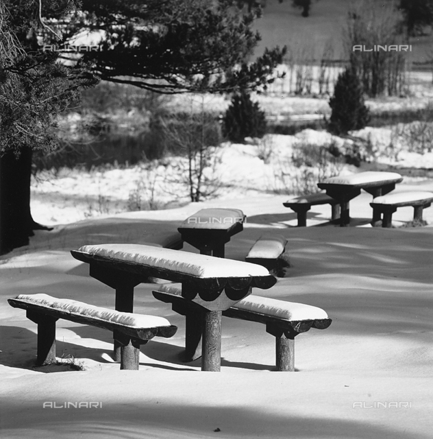 Tables and benches in the snow, in the area of Engadina, in Switzerland