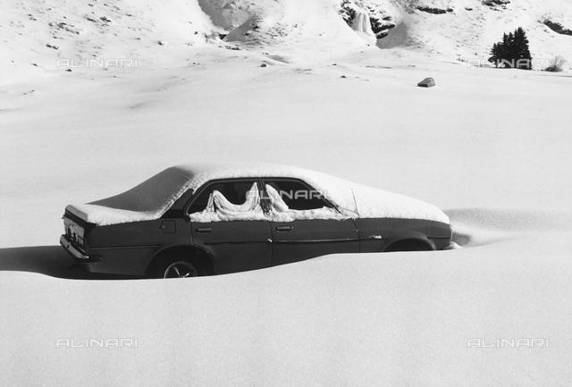 Car semi-covered in snow, in Celerina, in Switzerland
