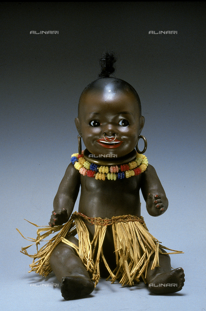 Black baby doll made in Germany in the 1930s. The doll is shown as a small African native with a ring in its nose, a straw skirt and a gaudy necklace and earrings