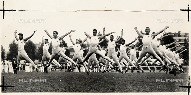 Lines of young men, photographed in mid-air, leap during gymnastic exercises.