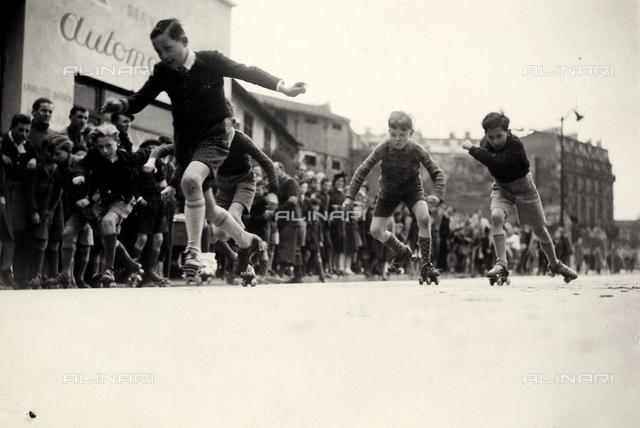 Children race on roller skates in a city street.